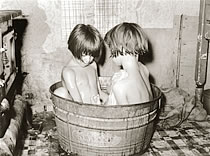 old-fashioned photo of kids bathing in a wooden tub