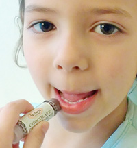 child applying lip balm