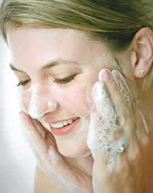 woman washing face with herbaria all natural soap